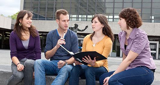 Vier Studierende sitzen vor dem Audimax und unterhalten sich angeregt.