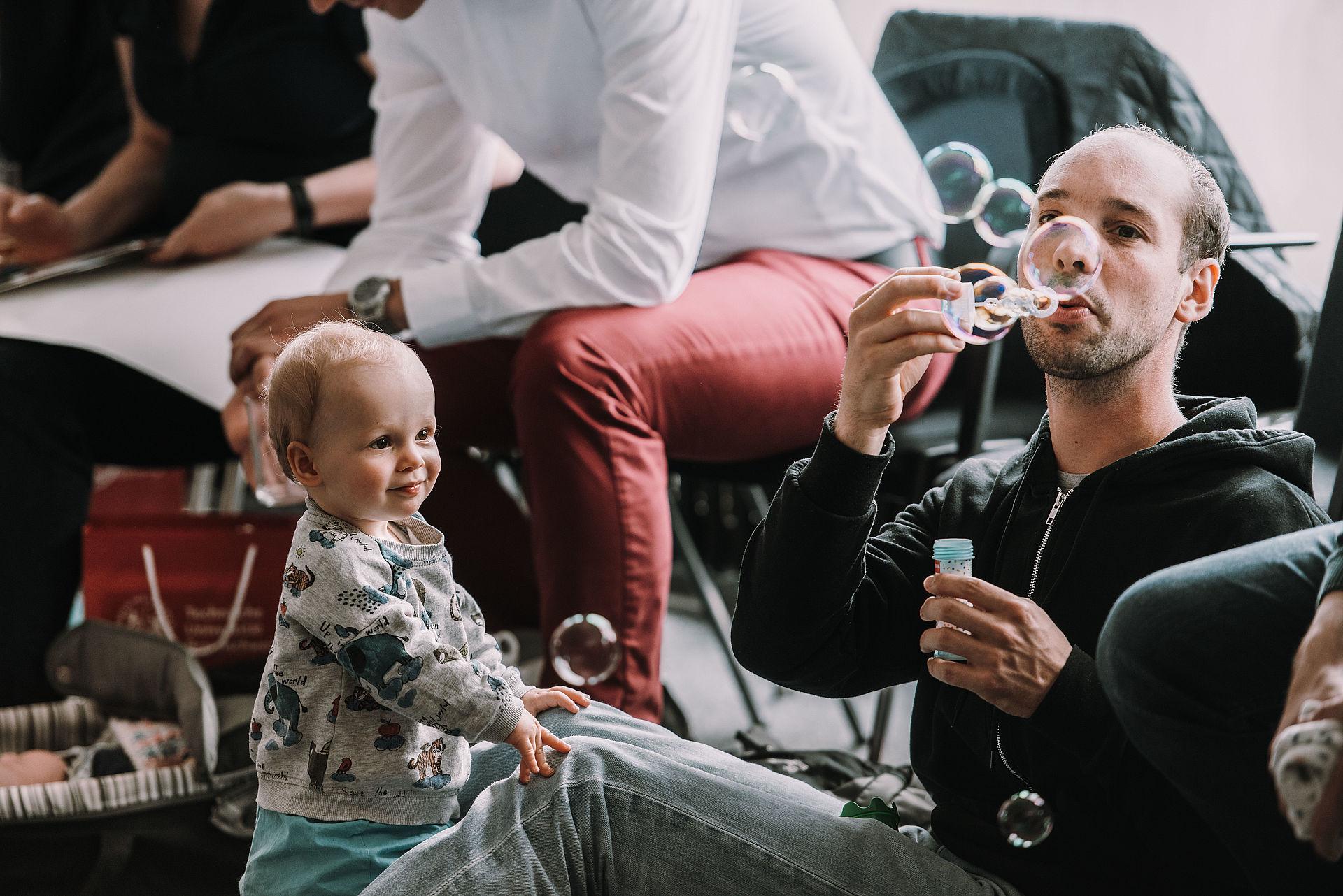 Staunendes Baby mit Papa und Seifenblasen