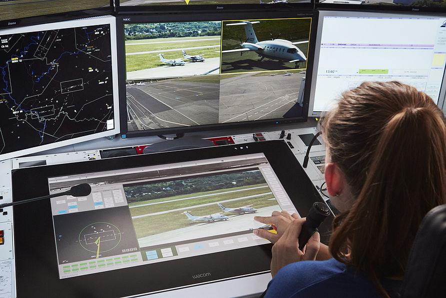 Auf ihren Displays kann die Fluglotsin das Vorfeld, die Rollwege und die Start- und Landebahn des Flughafens Saarbrücken sehen.