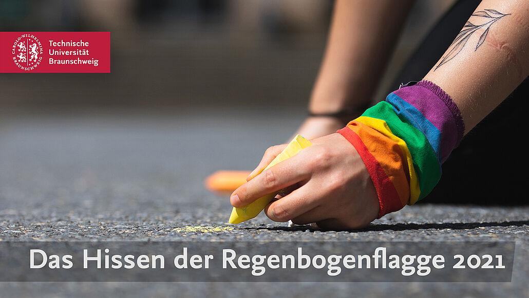 Eine mit der Regenbogenflagge umwickelte Hand malt mit gelber Kreide.